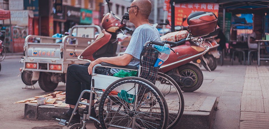 Man sitting in a wheelchair on a street in China.