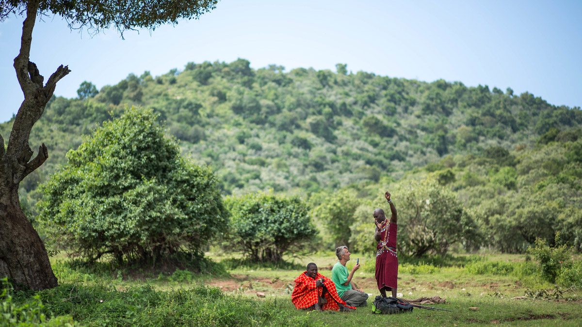 Masaai guide tells traveller a story out in the bush in Kenya
