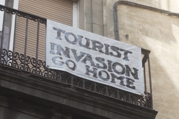 Film still of sign saying 'tourist invasion go home' hanging on balcony railings