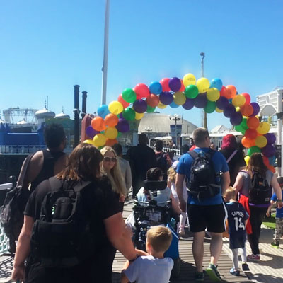 Families walking through an arc of balloons