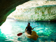 Kayaking through caves in Menorca. Photo by Audax Hotels